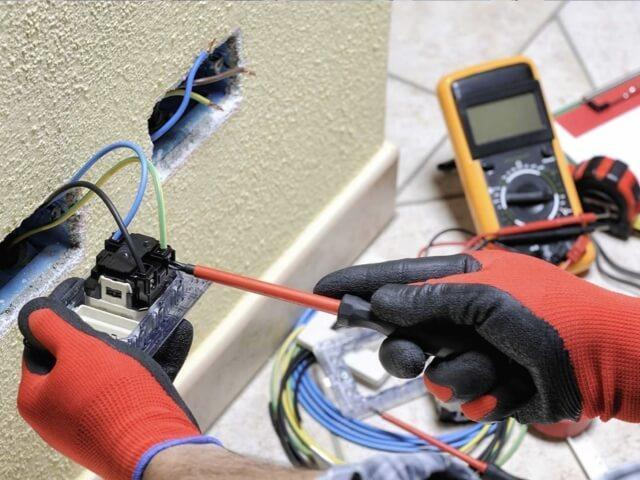 hands installing residential electrical outlet